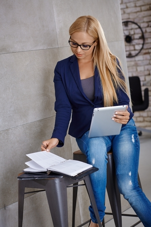 personal organizer: Busy young woman working on tablet, using personal organizer.
