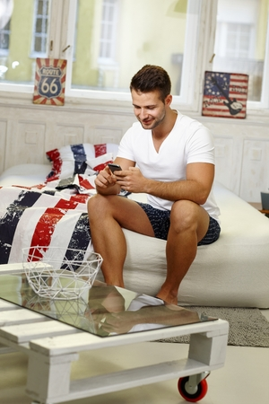 stubbly: Happy young man using mobilephone in the morning.