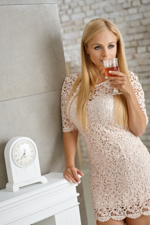 leaning against: Sexy blonde woman leaning against wall, holding a glass of wine. Stock Photo