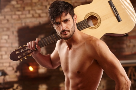 bare chest: Sexy young man holding guitar on shoulder, bare chest.