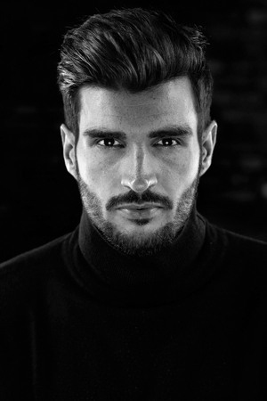 Black and white portrait photo of cool handsome young man looking at camera, dark tones.