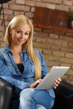 stockphoto: Attractive blonde woman sitting in armchair, using tablet computer.
