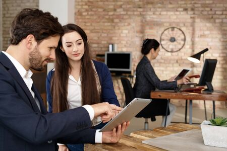 co work: Businesspeople using tablet computer, talking in office. Stock Photo