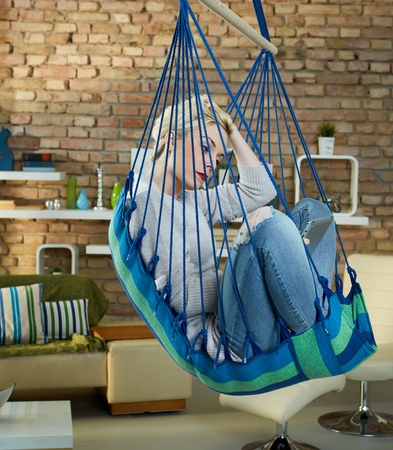 Young woman sitting in hammock like chair at home, using tablet computer. Stock Photo