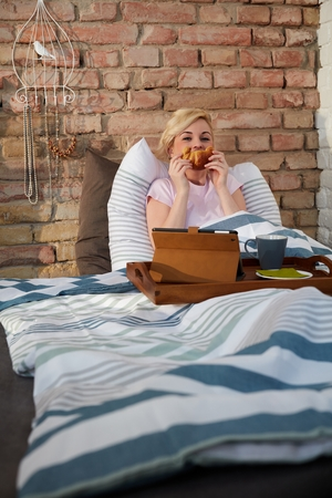nighty: Young woman forming smiley face of croissant in bed. Stock Photo