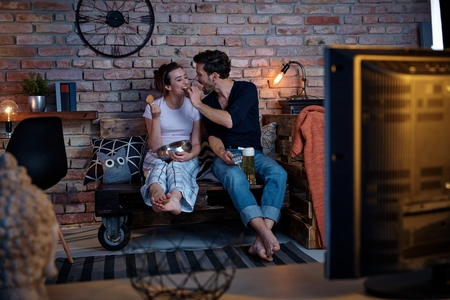 Romantic couple sitting front of tv at home, having fun.