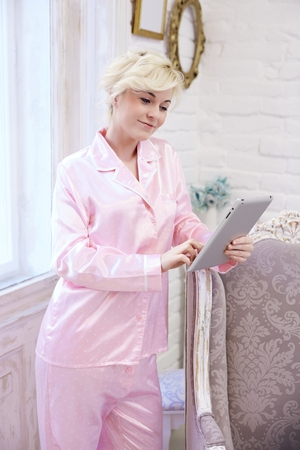 nighty: Young woman in pink silk pajamas using tablet computer at stylish home.