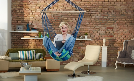 tailor seat: Young blonde woman using tablet computer, sitting in hanging chair at home. Stock Photo