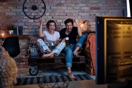 pareja viendo tv: Pareja emocionado viendo la televisi�n en casa, trepidaci�n.