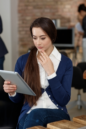 Young businesswoman using tablet computer, thinking. Stock Photo