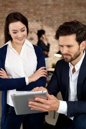 co work: Young businesspeople using tablet computer, smiling. Stock Photo