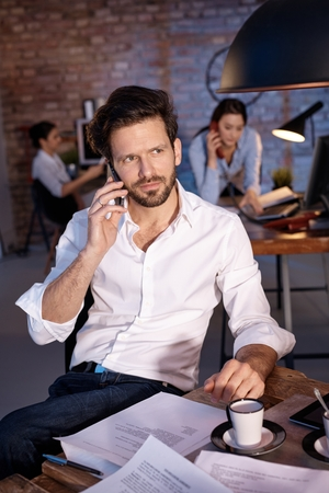 mobilephone: Young businessman talking on mobilephone, looking away. Stock Photo