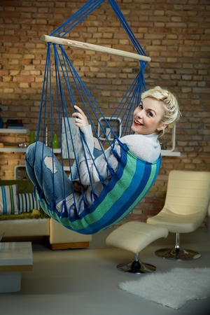 tailor seat: Happy blonde woman relaxing at home in hammock like chair. Stock Photo