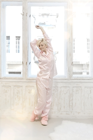 nighty: Young woman stretching front of window in pink pajamas. Full size. Stock Photo