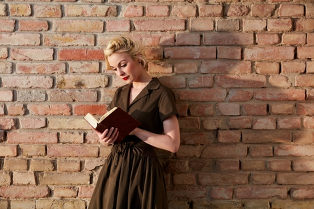 leaning against: Young blonde woman holding book, leaning against brick wall, reading.