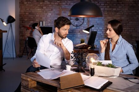 late twenties: Young businesspeople sitting at desk in office, working late. Stock Photo