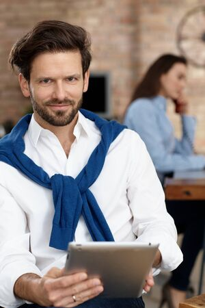Young businessman smiling at camera, holding tablet computer.