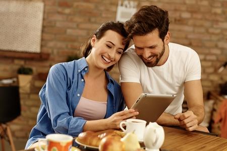 parejas enamoradas: Pareja feliz con tablet PC, sentado en la mesa del desayuno, se ríe.