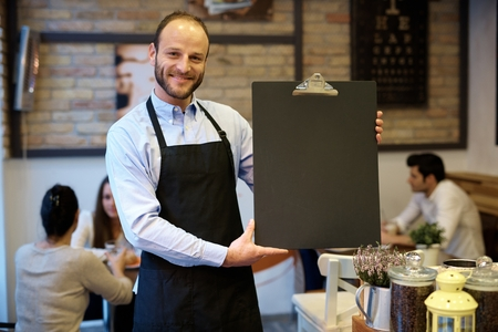 Happy waiter holding blank blackboard, smiling, looking at camera.