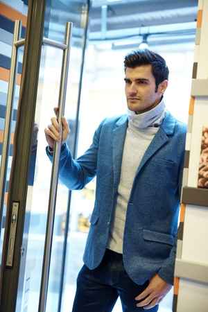 the entering: Handsome young man opening door, entering.