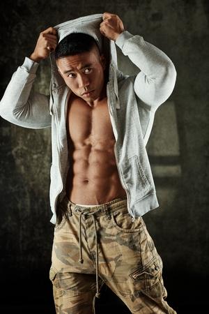 hoody: Male bodybuilder posing in hoody in studio.