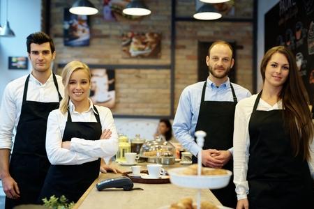 mandil: foto del equipo de camareros y camareras de pie en el delantal en la cafetería.