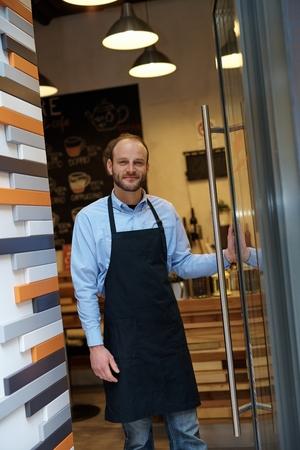 invitando: camarero invitando a la cafeter�a con la apertura de la puerta de entrada sonriendo.