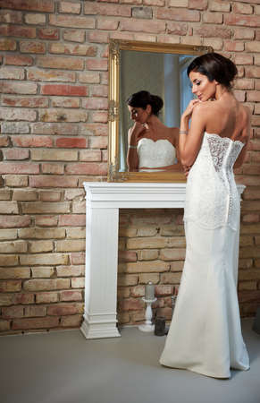 mirror: Beautiful bride standing front of mirror, photographed from behind. Full size. Stock Photo