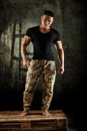 musculoso: Hombre asiático joven muscular que presenta en estudio. Tamaño completo. Foto de archivo
