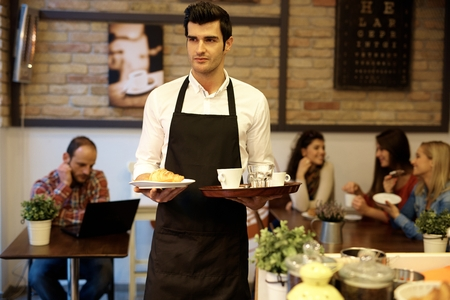 cafeteria tray: Handsome young waiter working in cafeteria, serving guests, wearing apron.