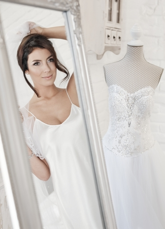 dressing up: Beautiful bride dressing up on wedding-day, looking at herself in mirror.