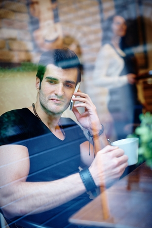 mobilephone: Young man drinking and talking on mobilephone in cafeteria. Photographed from outside. Stock Photo