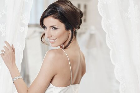 stockphoto: Attractive young bride in white slip, smiling.