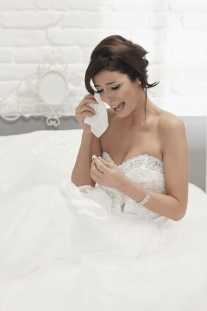 heartbroken: Heart-broken bride holding engagement ring, crying on wedding-day, looking unhappy. Stock Photo