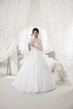 Piękna panna młoda stoi w sypialni w stroju, uśmiecha się szczęśliwy. Pełny rozmiar.