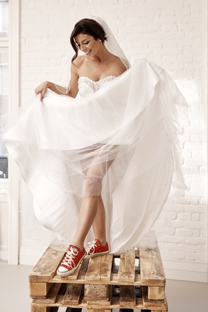 joyous: Provocative bride wearing red sneakers and wedding gown. Standing on pallet.