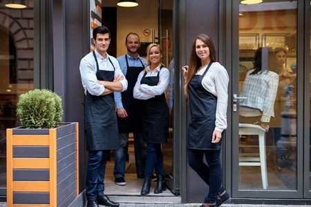 Happy waiters and waitresses standing at the entrance of cafeteria, smiling, looking at camera, wearing apron. Stock Photo
