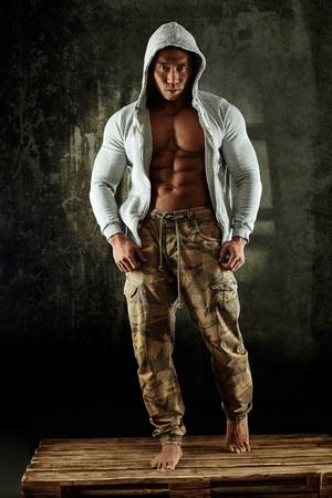 Asian male bodybuilder posing in studio wearing hoody. Full size.