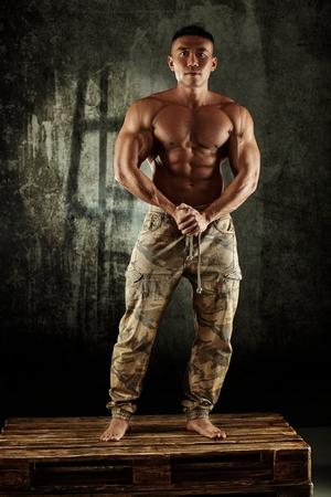 nackte brust: Asian männliche Bodybuilder mit nacktem Oberkörper posiert im Studio.