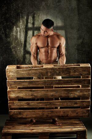 Asian male bodybuilder posing with pallet, bare upper body.