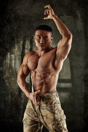 asian bodybuilder: Asian male bodybuilder posing with bare upper body, looking at camera.