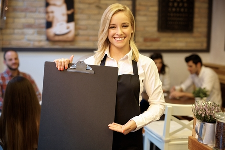 stockphoto: Cheerful blonde waitress holding blank blackboard, smiling happy, looking at camera.