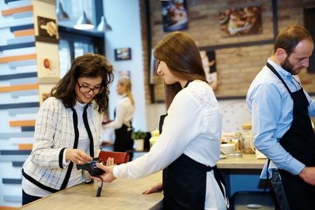 pagando: huésped femenina pagar con tarjeta de crédito en la cafetería.