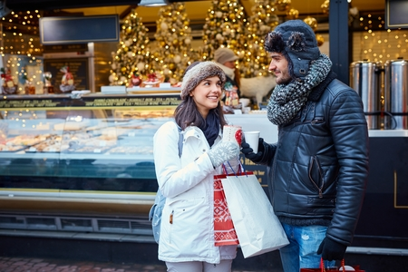 good color: Young couple having hot drink at wintertime on the street.