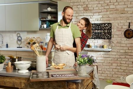 mandil: feliz pareja cocinar juntos en la cocina, mujer tieing delantal en el hombre. Foto de archivo