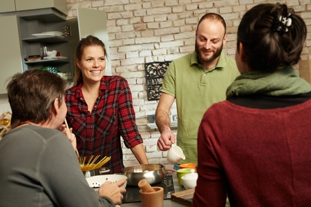four people: Happy couple and friends talking and cooking together in kitchen.