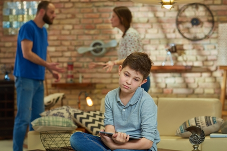 Sad boy sitting on sofa with tablet while parents shouting, arguing at background. Stock Photo