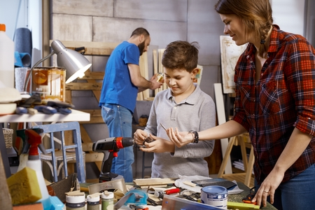 tinkering: Parents and son tinkering together in workshop.