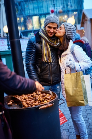be kissed: Kissing young couple walking on the street at wintertime, buying roasted chestnuts.