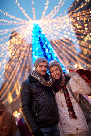 Outdoor portrait of happy young couple doing christmas shopping at christmas fair. Stock Photo